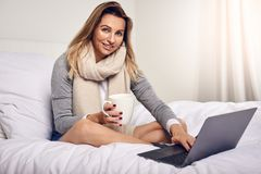 Attractive woman sitting on her bed. Wrapped in a warm knitted scarf with coffee and an open laptop computer smiling at the camera Stock Photography