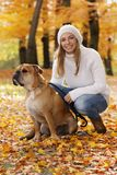 Attractive woman sitting with her dog in autumn surrondings royalty free stock photo