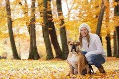 Attractive woman sitting with her dog in autumn surrondings royalty free stock images
