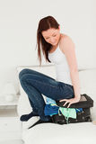 Attractive woman sitting on her suitcase Stock Images