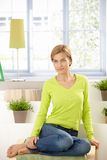Attractive woman sitting at home in vivid green Stock Image