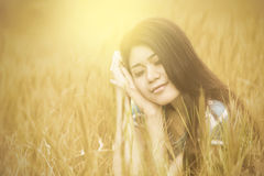 Attractive woman sitting on meadow alone Royalty Free Stock Image
