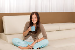 Attractive woman sitting on modern home sofa Stock Images