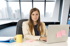 Attractive woman sitting at office chair working at laptop computer desk Stock Images