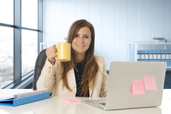 Attractive woman sitting at office chair working at laptop computer desk Stock Photo