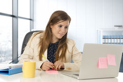 Attractive woman sitting at office chair working at laptop computer desk Royalty Free Stock Photo