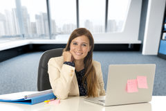 Attractive woman sitting at office chair working at laptop computer desk Stock Photos