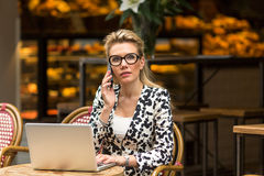 Attractive  woman sitting in outdoor cafe with laptop talking on the mobile phone. Royalty Free Stock Photography