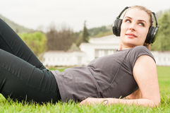 Attractive woman sitting outside wearing headphones to listen mu Royalty Free Stock Photography