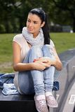 Attractive woman sitting in park Stock Images