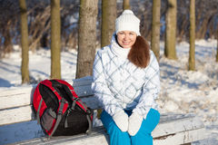 Attractive woman sitting on park bench at winter Stock Photo