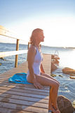 Attractive woman sitting on pier. Attractive woman in white bathing suit sitting on wooden pier in nordic country during summer Stock Images