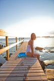 Attractive woman sitting on pier Stock Photos