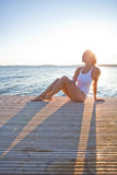 Attractive woman sitting on pier. Attractive woman in white bathing suit sitting on wooden pier in nordic country during summer Stock Photos