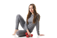 Attractive woman in sitting position two red dumbbells keeping in one hand in gray thermal underwear. Stock Photo
