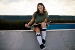 Attractive woman sitting on ramp at skate park. Urban girl with skateboard relaxing and spending time at the skate park Royalty Free Stock Photos