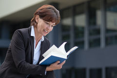 Attractive woman sitting reading a book Stock Photos