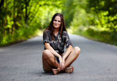 Attractive woman sitting on the road Stock Image