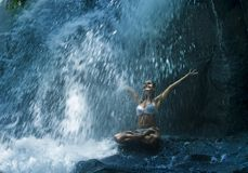 Attractive woman sitting at rock in yoga pose for spiritual relaxation serenity and meditation at stunning beautiful waterfall and royalty free stock images
