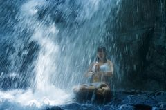 Attractive woman sitting at rock in yoga pose for spiritual relaxation serenity and meditation at stunning beautiful waterfall and. Rain forest in Bali Summer royalty free stock image
