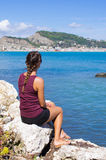 Attractive woman sitting on the rock, Zakynthos, Greece Stock Image