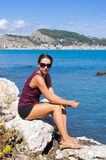 Attractive woman sitting on the rock, Zakynthos, Greece Royalty Free Stock Images