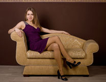 An attractive woman sitting on sofa royalty free stock photography