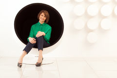 Attractive woman sitting on spherical chair with hands on knees Stock Photography