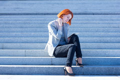 Attractive woman sitting on the stairs on the street and working on a tablet Royalty Free Stock Photography