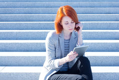 Attractive woman sitting on the stairs on the street and working on a tablet Stock Photos