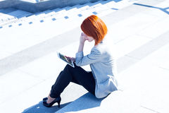 Attractive woman sitting on the street on the stairs with tablet Royalty Free Stock Image