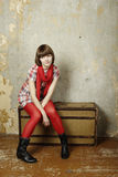 Attractive woman sitting on a suitcase Stock Photos