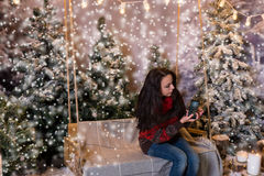Attractive woman sitting on a swing and taking a photo of spruce Stock Photo