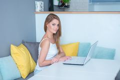 Attractive woman sitting using a laptop at home Stock Images