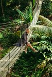 attractive woman sitting on wooden suspension bridge royalty free stock photography
