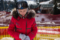 Attractive woman in ski suit, with helmet and ski goggles puttin Stock Image