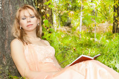 Attractive woman sleeping with book. Against a tree Stock Images