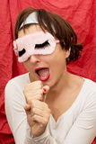 Attractive woman in sleeping mask imitates singing into a microp Stock Image