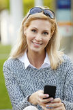 Attractive woman with smart phone. Close-up portait of casual businesswoman sitting in front of office building on the street while texting message on her smart Stock Images