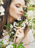 Attractive woman smelling wild flowers Royalty Free Stock Photos