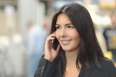 Attractive woman smiling as she chats on a mobile Royalty Free Stock Photos