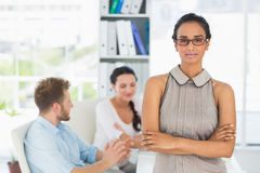 Attractive woman smiling at camera while colleagues chat at desk Royalty Free Stock Photos