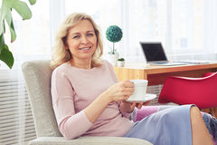 Attractive woman smiling and drinking coffee while sitting on so Royalty Free Stock Photography