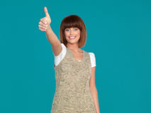 Attractive woman smiling with her thumb up. Beautiful, young woman, smiling and showing her thumb up, on blue background Stock Image