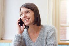 Attractive woman smiling with mobile phone at home Royalty Free Stock Image