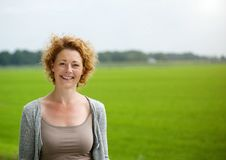 Attractive woman smiling outdoors by green countryside Royalty Free Stock Photography