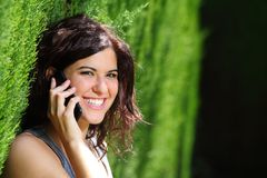 Attractive woman smiling on the phone in a park Stock Photography