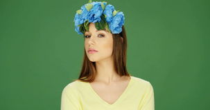 Attractive woman smiling and posing in a floral headdress. Video of an attractive young woman smiling and posing for the camera while wearing a blue floral stock footage