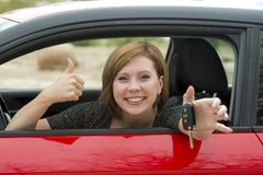 Attractive woman smiling proud sitting at driver seat holding and showing car key in new automobile buying and renting Royalty Free Stock Photos