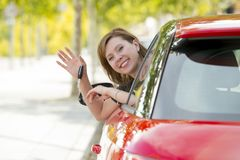 Attractive woman smiling proud sitting at driver seat holding and showing car key in new automobile buying and renting Stock Photo